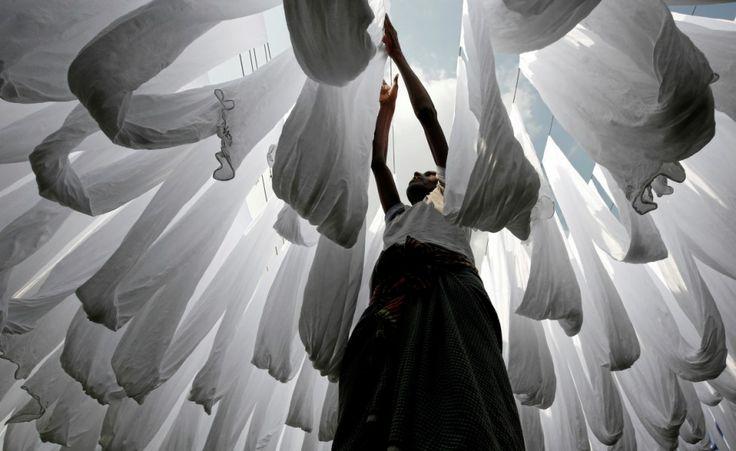 Un lavoratore stende al sole i tessuti dopo averli lavati a Narayanganj, in Bangladesh