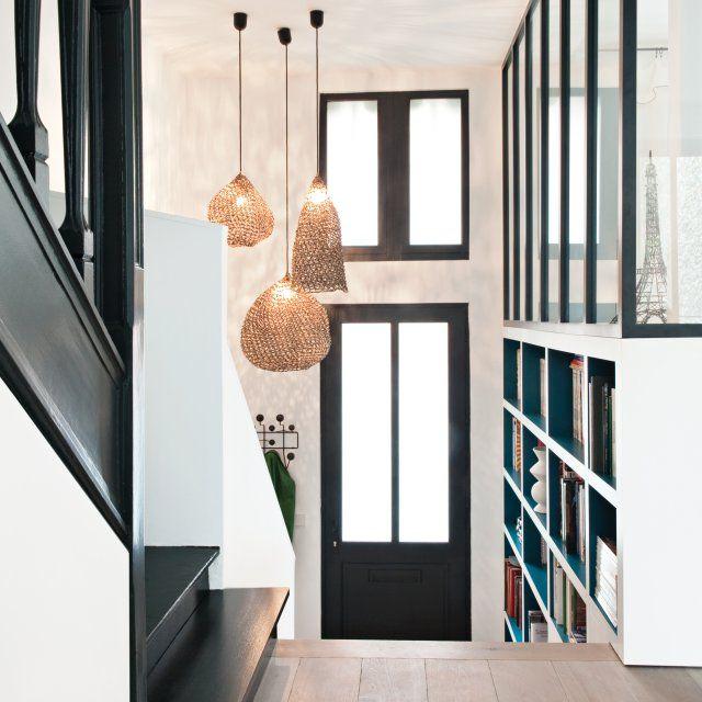 Avec un léger décalage de niveau, cette cage d'escalier profite d'un sas dans lequel les architectes ont conçu une élégante bibliothèque sur mesure avec l'intérieur laqué de bleu. Les suspensions apportent une jolie lumière dans l'escalier.