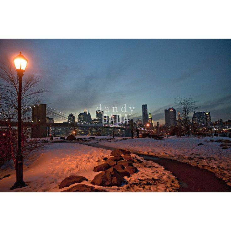 """The big-pink apple di Piergiorgio PirroneE' l'ora del tramonto a Brooklyn. Il fotografo Piergiorgio Pirrone attratto dallo skyline newyorkese, accresce l'impatto suggestivo della metropoli con il grandangolo. L'osservatore è invitato a percorrere il vialetto e immergersi nella caotica """"Grande Mela"""".  New York 2010-11."""