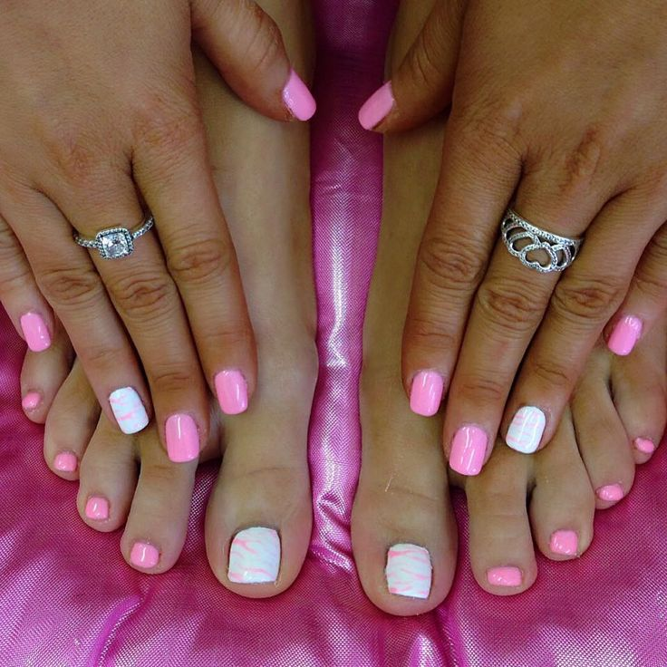 Matching manicure and pedicure in bright pink with white and pink marbled accent nails