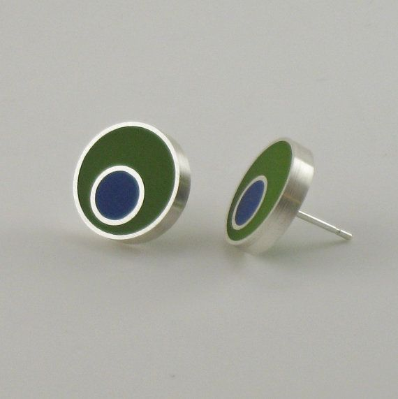 A dark blue dot of resin, surrounded by a band of silver, is nestled in a silver framed circle of olive green resin. These contemporary earrings,