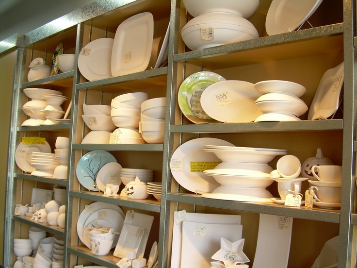 Sleek shelves full of contemporary bisque pottery shapes.