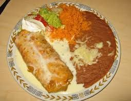 CHICKEN CHIMICHANGAS  Chi Chi's Copycat Recipe   Serves 4    2 tablespoons unsalted butter  4 tablespoons vegetable oil  1 yellow onion,...