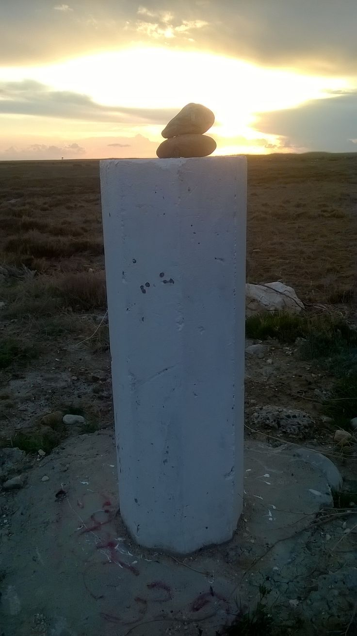 Stones stacked carefully on a concrete pedestal. Are they in alignment with some other feature in the landscape? Do they mark a site of some religious significance? Is this an important boundary marker?