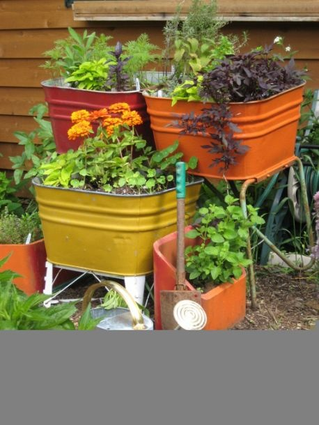 great idea for upcycling old wash tubs and chimney flues in to a colorful garden area.