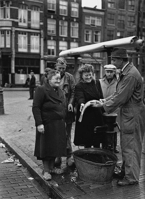 Visverkoper op straat, Amsterdam, 11 november 1947 kijk opoe met haar sloffen!!.