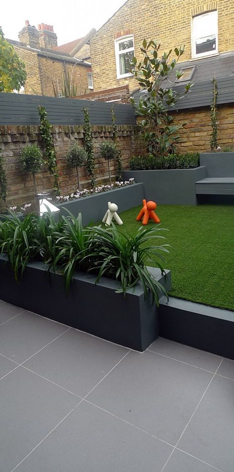 Raised beds grey colour scheme agapanthus olives artificial grass porcelain grey tiles Floating bench lighting Balham Wandsworth Battersea Vauxhall Fulham Chelsea London