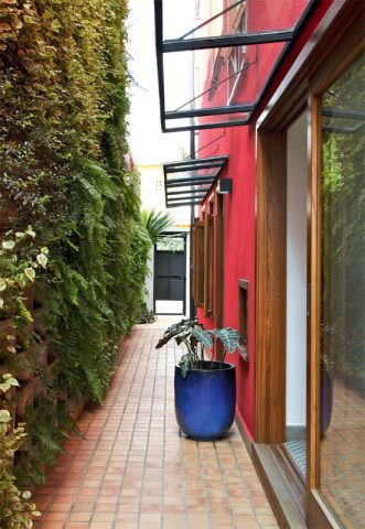 No corredor, as marquises de ferro e vidro deixam a luz entrar e o jardim vertical (Neo-Rex) disfarça a altura do muro.
