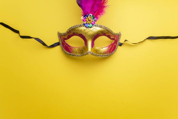 Colorful mardi gras or carnivale mask on a yellow background stock photo
