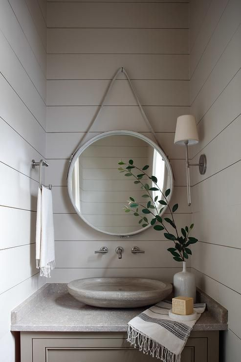 Chic white and gray powder room boasts shiplap walls accented with a leather convex mirror illuminated by a Camille Long Sconce placed over a wall-mount faucet and a gray washstand topped with a gray oval vessel sink.