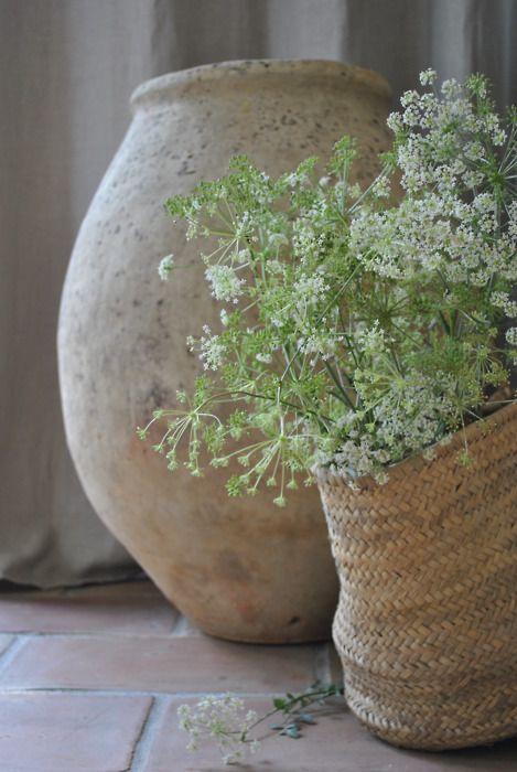 Pequeñas flores blancas en cesta de mimbre