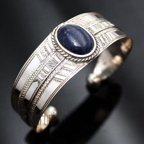 Bracelet touareg en argent gravé avec serti d'une pierre de Lapis Lazuli bleue de forme ovale.Matières : argent et lapis-lazuliDimensions : 3.5 cm large . Taille de la pierre : 3 cmOrigine : artisan touareg d'Agadez, Niger