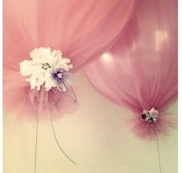 Satin balloons wrapped in tulle and tied with flowers and string.