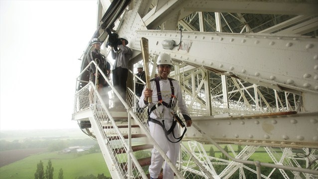 Comedian John Bishop holds the Olympic Flame at Jodrell Bank Observatory during Day 13 of the London 2012 Olympic Torch Relay.