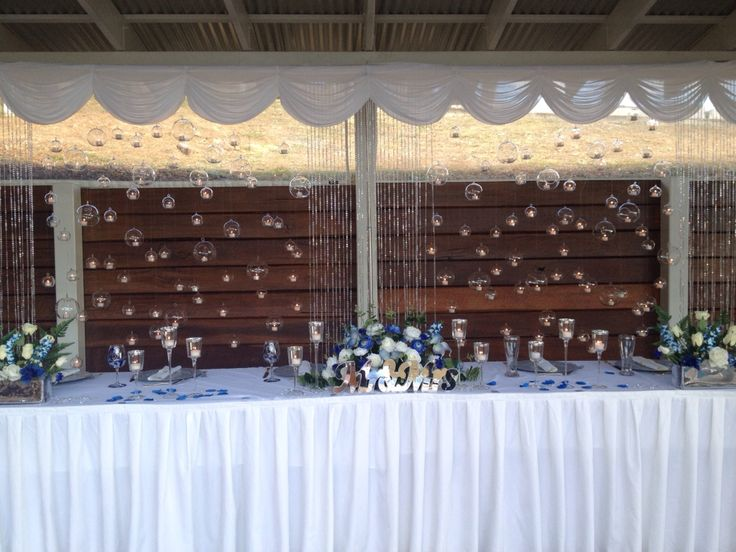 Modern wedding, Ombré Blue wedding, Wedding bubbles, custom design backdrop displays are a specialty at www.allperfectlyplanned.com hanging tea light backdrop with crystal  draping, hanging crystal drops , and white swagging with blue galaxy orchids, Americana ceremony chairs, white aisle carpet and shepherd hooks with hanging glass balls. Polaroid guest book, individual mud cakes , navy blue wedding dress.  Branell Homestead Laidley Queensland wedding