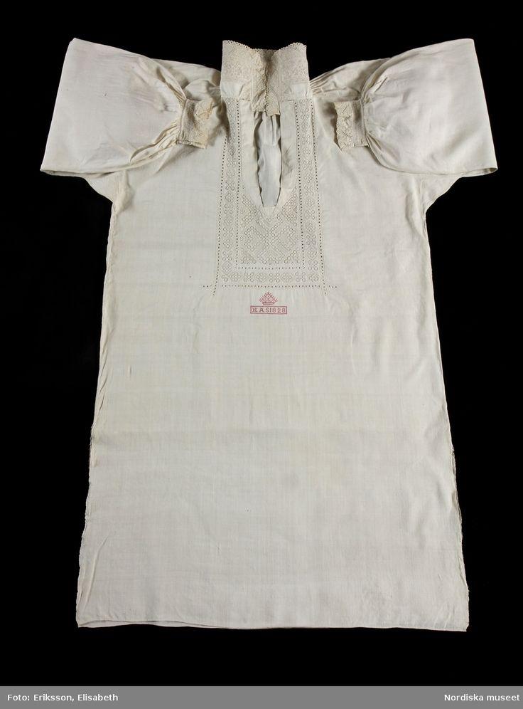 """Skjorta av vit linnelärft. På halva kragbredden broderad bård i vitt och ljusgrått lingarn i tät utdragssöm av skånsk typ.   Runt sprundet och nedanför broderi i utskårssöm och utdragssöm  samt något plattsöm och hopdragssöm med lingarn. Nedanför broderiet märkt K A S 1828 under """"krona"""" med rosa bomullsgarn i korssöm.   En mycket typisk  brudgumsskjorta av rikaste slag från Ingelstads hd. Broderi och sömmar mycket välgjorda."""