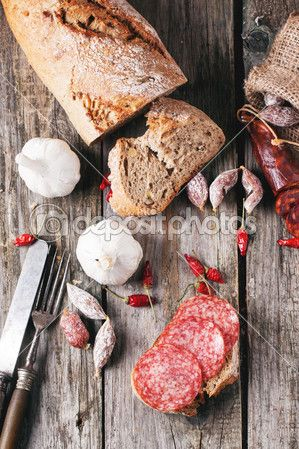 вид сверху на множестве колбасы салями свежего хлеба, чеснока и красного острого перца Чили служил с vintage посуды на старый деревянный стол. смотреть серии