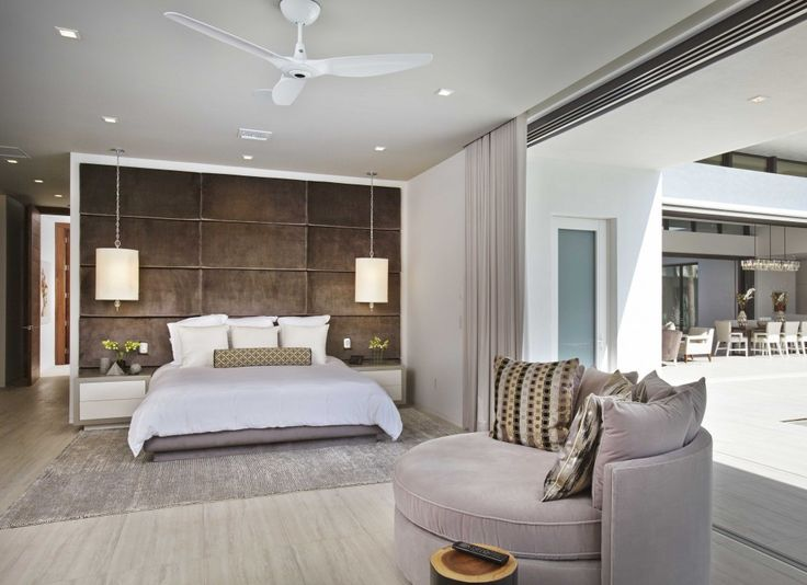 A quiet oasis, the master bedroom emphasizes its streamlined spaciousness with a single wood-lined wall that acts as an oversized headboard.