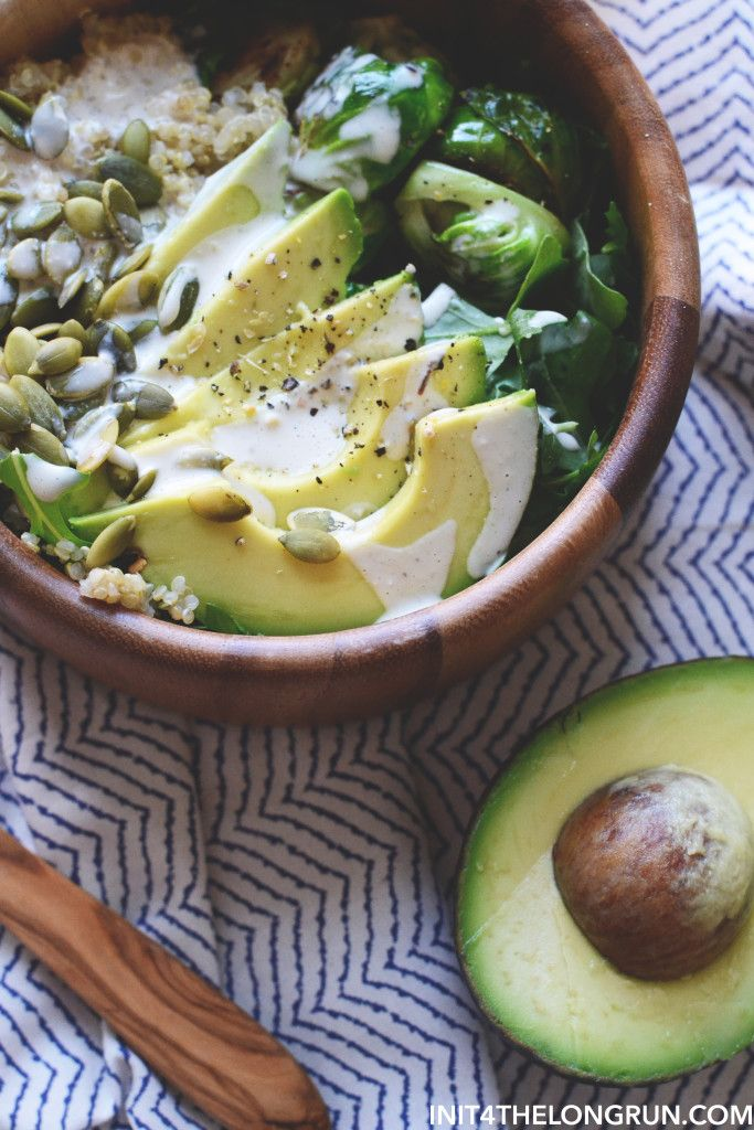 Avocado Quinoa Harvest Bowl | Cooked quinoa, sauteed brussel sprouts, arugula, sliced avocado, dressed with olive oil and tahini, garnished with pumpkin seeds.