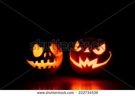 Scary Halloween pumpkins isolated on a black background. Scary glowing faces…