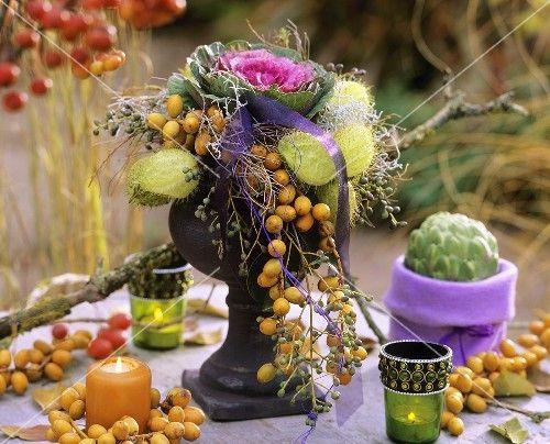 Gesteck mit Zierkohl, Früchten der Seidenpflanze und Datteln