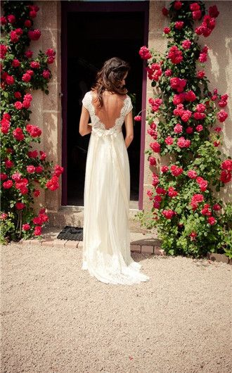 What a gorgeous wedding dress! And lovely flowers above the doorway. #weddingdress #weddinginspiration