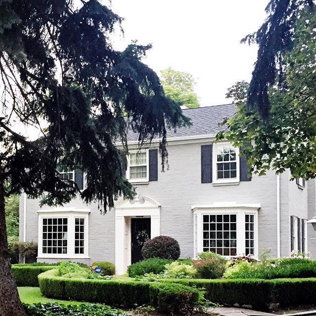 Gray brick. White trim, door casing and dark blue shutters