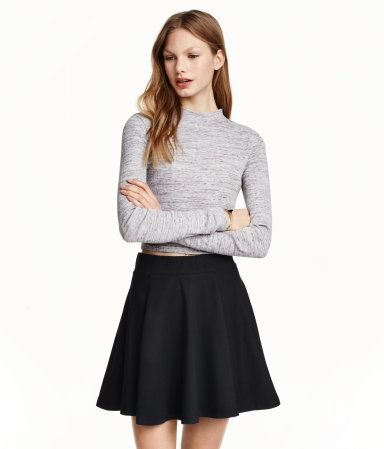 Een korte, klokkende rok van elastisch tricot met breed elastiek in de taille. Ongevoerd.