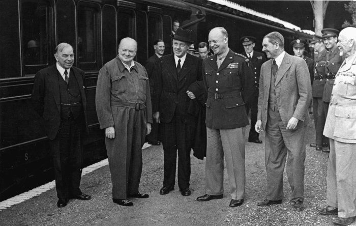 Five Commonwealth Prime Ministers and the Supreme Allied Commander in Europe, General Dwight D Eisenhower of the US Army, during a halt of the train taking them to inspect Allied troops just before the Normandy Landings. From left to right: William Lyon Mackenzie King (PM of Canada), Winston Churchill (PM of the UK), Peter Fraser (PM of New Zealand), Eisenhower, Godfrey Huggins (PM of Southern Rhodesia) and Jan Christian Smuts (PM of South Africa). Photographer unidentified.