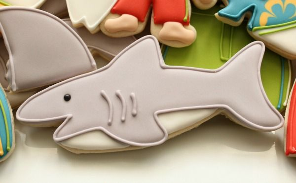 """<p>Take your theme next level with these adorable shark cookies. <a href=""""http://www.sweetsugarbelle.com/2013/06/simple-shark-cookies/"""" target=""""_blank"""">Get the recipe here.</a></p>"""
