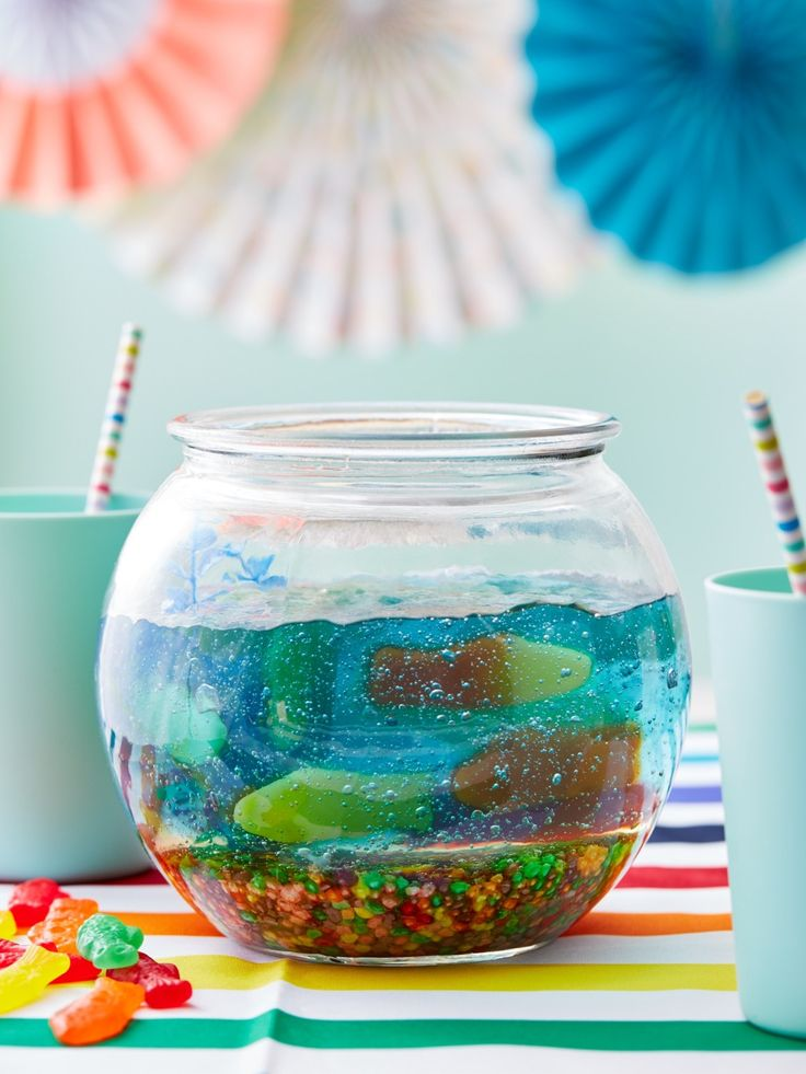 Perfect for Shark Week, this jello fish bowl recipe is gluten-free and super easy to make as party food. To make this fun jello fishbowl from under the sea, you'll need flat lemon-lime soda, multi-color Nerds candy, blue food coloring and fish gummy candies