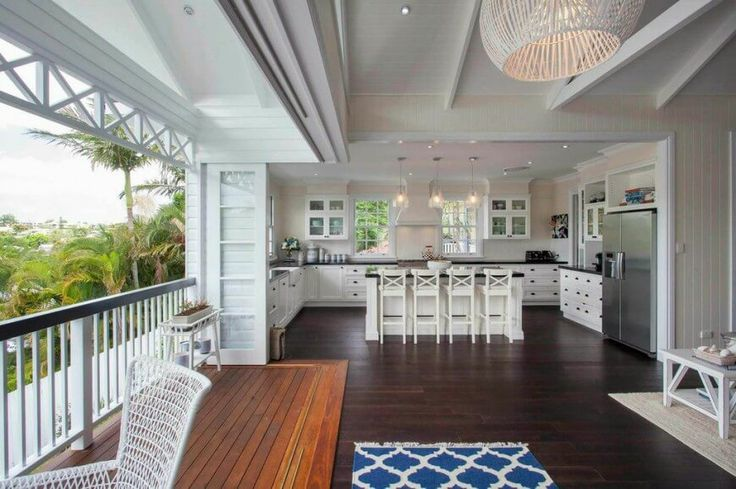 The balcony is included in the area. The glass doors can be pulled shut to enclose the main portion of the house during less than beautiful weather. From this angle, we can see the entirety of the spacious U-shaped kitchen with custom cabinetry and an eat-in kitchen bar.