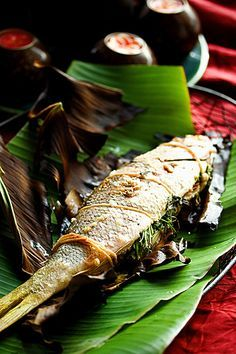 Grilled whole fish on banana leaf with cilantro and thai basil