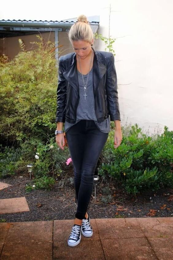 26 Great Fall Outfits: Ideas To Try Already This Autumn/Winter Season: Woman in a garden wearing black distressed skinny jeans, loose-fitting gray T-shirt, black leather jacket and Converse sneakers
