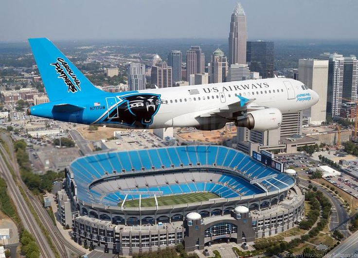 US Airways Airbus A319-112 N717UW in Carolina Panthers livery, flying over the team's home venue, Bank of America Stadium in Charlotte, circa 2007.