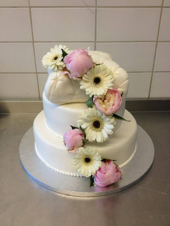 Bryllupskake i 3 etg. hvor den øverste kaken har puteform. Dekorert med ekte blomster. Pris 3900,-
