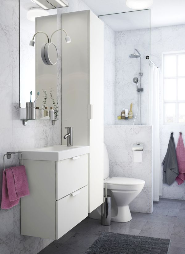 A White Small Bathroom With A White High Cabinet A Mirror And A Wash Stand With Two Drawers