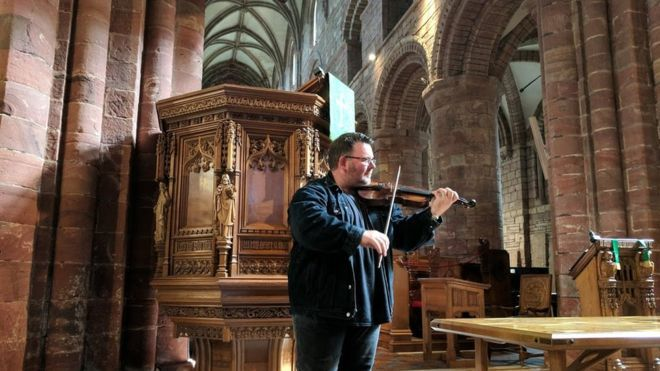 A fiddle which was made from the wreckage of a sunken battleship almost 100 years ago has been played in St Magnus Cathedral after being returned to Orkney for restoration. The instrument was made in Flotta from wood from HMS Vanguard. Its history emerged after Gayle Duggan, from Edinburgh, bought the old battered fiddle for £20 at a car boot sale. She found a scrap of paper stuck inside, which took months to decipher due to water damage.