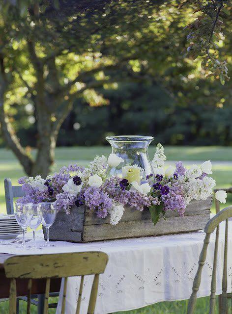 Un arreglo sencillo en lilas, celestes y blancos, ideal para una mesa en el campo.