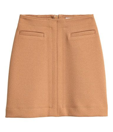 Beige. Knee-length skirt in a woven fabric with decorative pockets at front and a visible zip at back. Unlined.