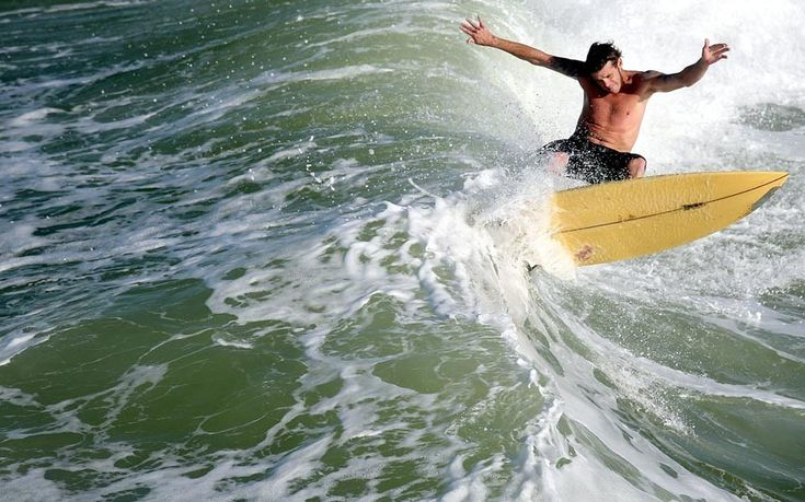 A surfer rides a wave off Panama City Beach, FloridaPicture: AP Photo/The News Herald, Andrew Wardlow