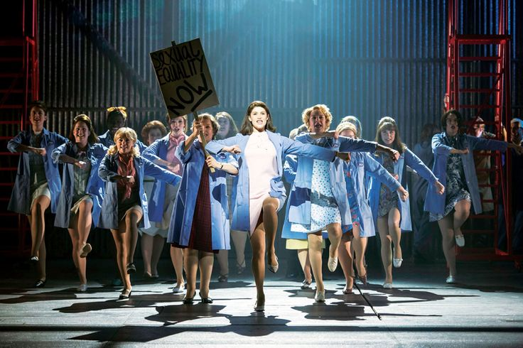 The women of made in dagenham marching towards the stage as they fight for women equal pay