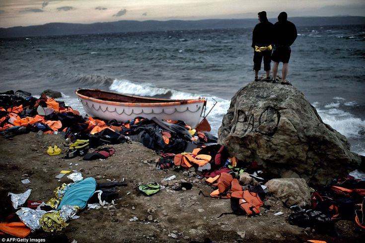 Survivors: Two men look out to sea after the terrifying ordeal, on the Greek island of Lesbos, after a boat carrying migrants and refugees sank