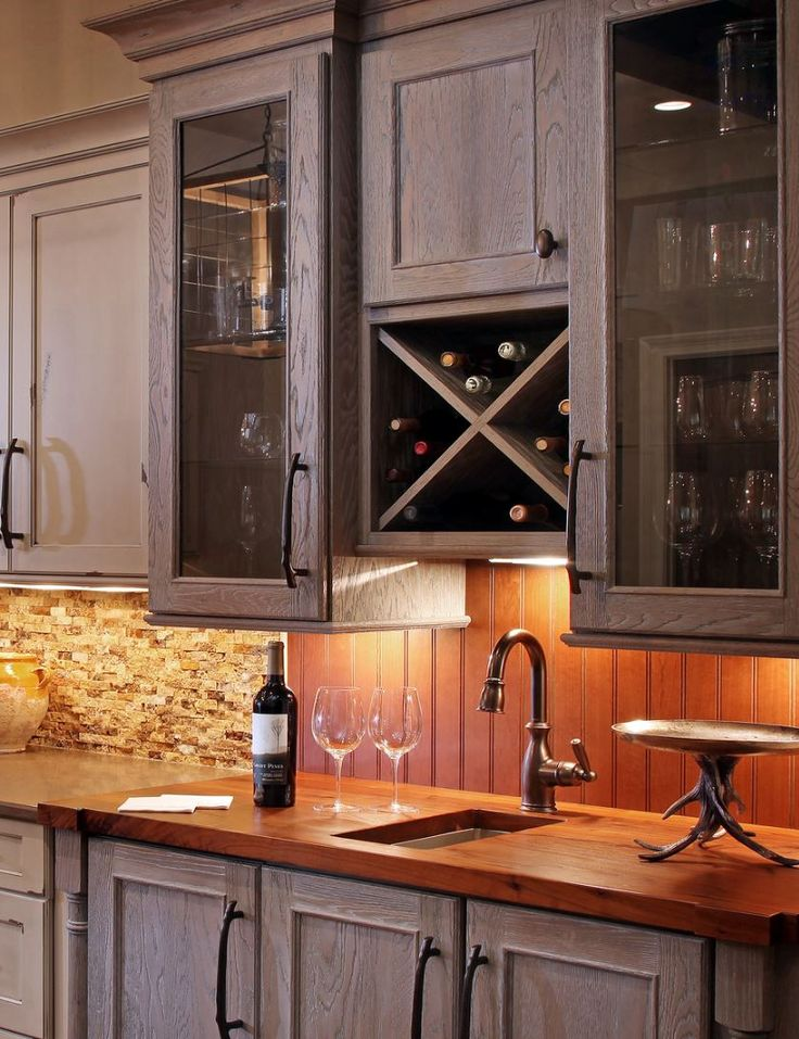 A rustic and warm Dura Supreme Cabinetry kitchen with a bar are with an X Wine rack about the wet bar sink and storage space for wine glasses.