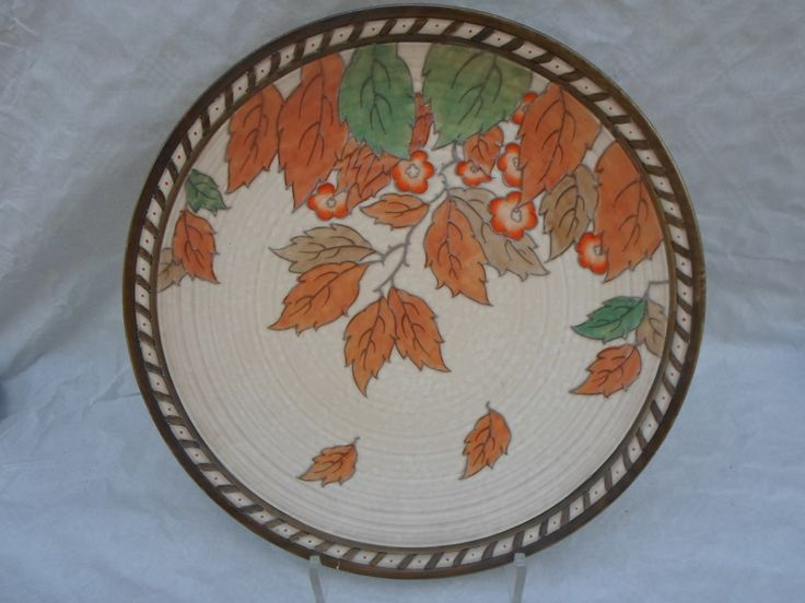 A 1930s Crown Ducal wall plaque, designed by Charlotte Rhead in the 4921 Golden Leaves pattern, having a tube-lined decoration of autumnal leaves on a buff ground, printed and tubed marks verso to include a Rhead facsimile signature, 37cm diameter