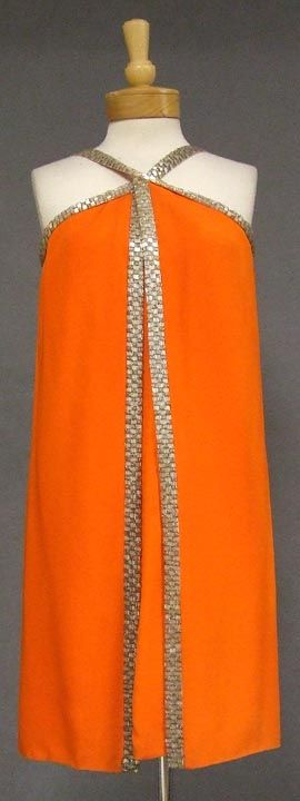 1960's Sarmi cocktail dress in a heavyweight tangerine crepe edged with beads. Straight, simple cocktail dress with an additional wrapped panel on top and a beaded halter strap. Via Vintageous