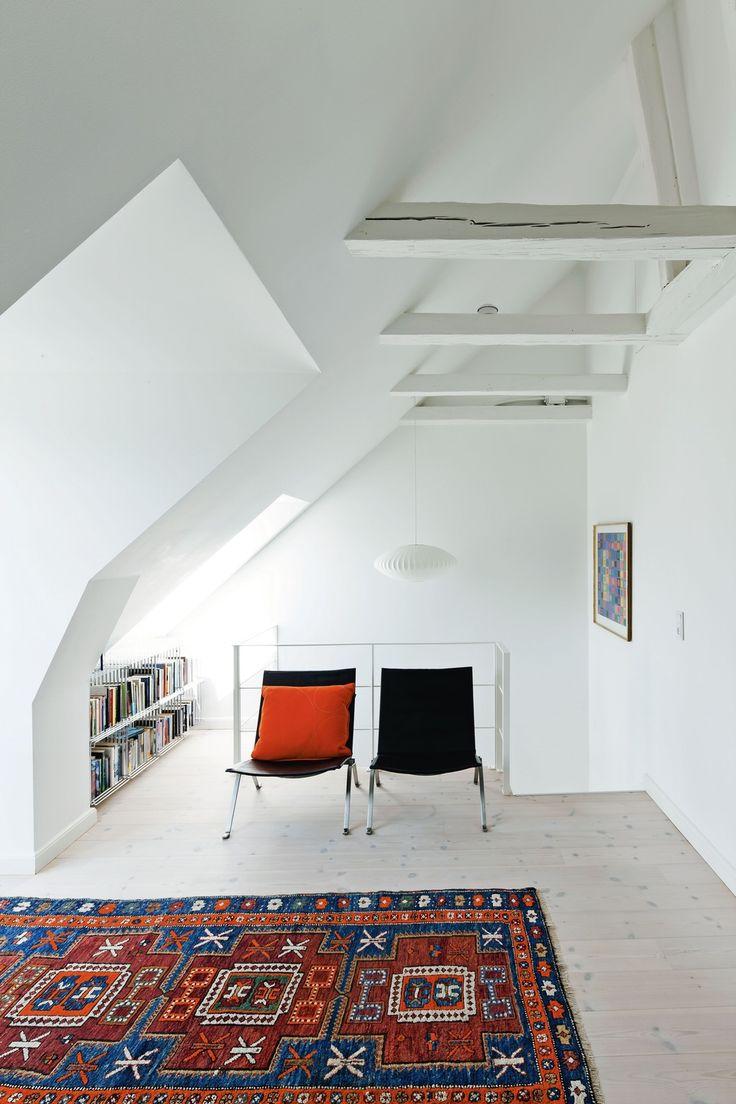 De flotte PK 22-stole fra Fritz Hansen har fået plads ved siden af en række trådreoler af Verner Panton. Lampen over trappen er en George Nolton papir-lampe fra CasaShop og tæppet er et arvestykke.