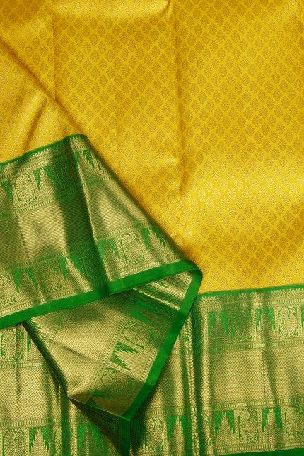 This yellow kanchivaram silk has a textured geometrical weave in gold zari all over . The complementing border and pallu are in green that has an intricately woven design in gold zari giving it a l…