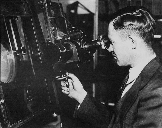 Clyde Tombaugh, discoverer of Pluto, peers into an instrument. CREDIT: Lowell Observatory