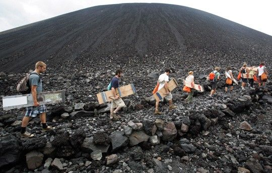 Travelers climb Nicaragua's Cerro Negro volcano in order to sandboard down the slopes. Craziness!